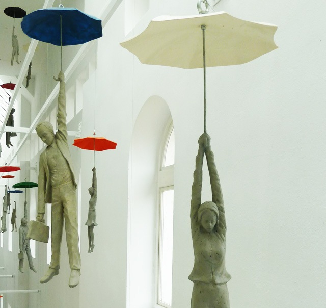 Cement People dangling from umbrellas Michal Trpak 6