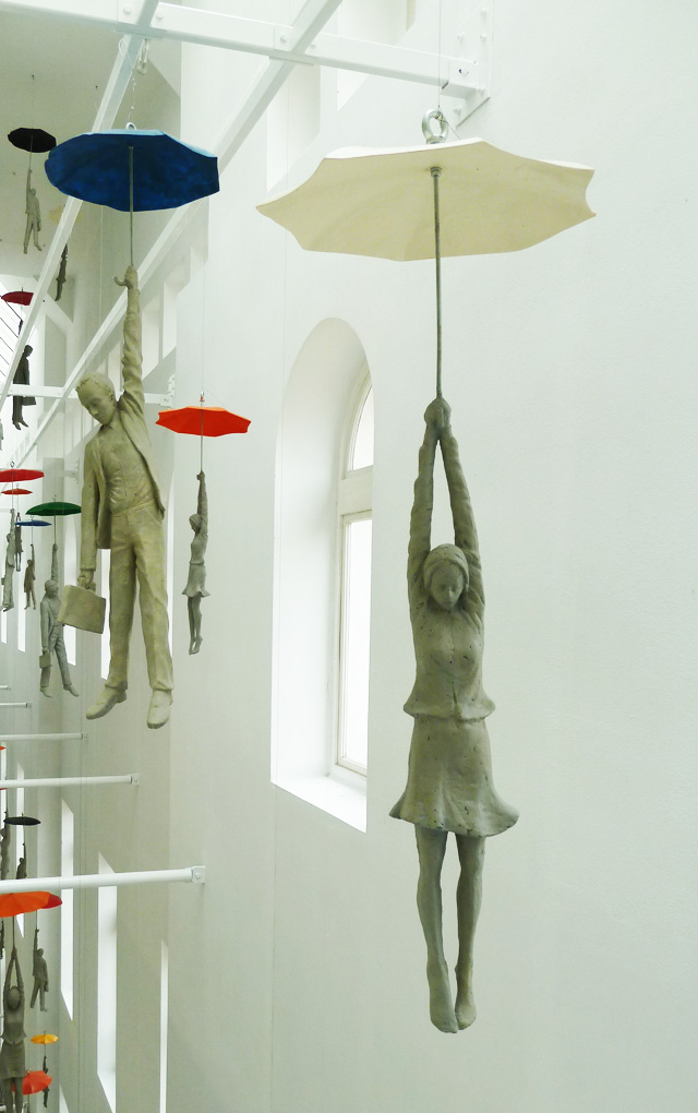 Cement People dangling from umbrellas Michal Trpak